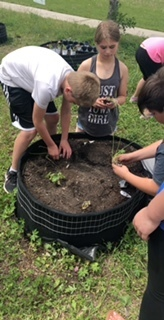 Students in Learn, Play, Grow planting their garden boxes